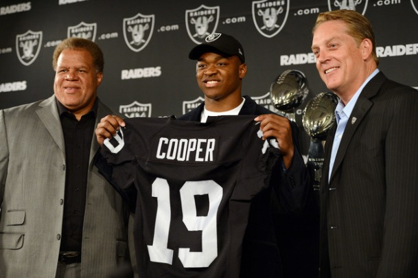 The Oakland Raiders' 2015 first round draft pick, wide receiver Amari Cooper, center, of the University of Alabama, holds his new jersey with General Manager Reggie McKenzie, left, and Head Coach Jack Del Rio as he is introduced to the public and media at Raiders headquarters in Alameda, Calif., on Friday, May 1, 2015. (Dan Honda/Bay Area News Group)